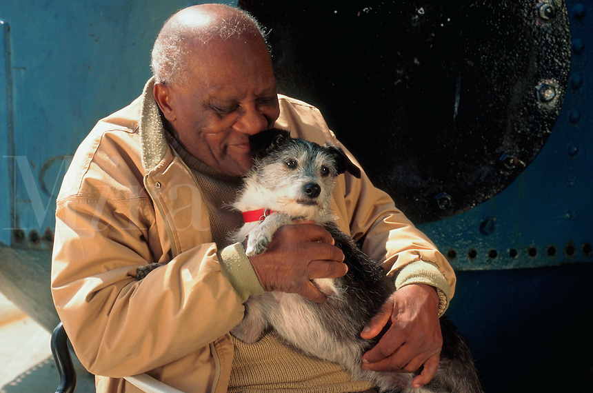 Pet therapy dog with elder African-American man.