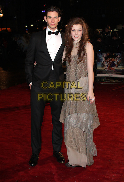 "BEN BARNES & GEORGIE HENLEY .Attending The Royal Film Performance 2010: The World Premiere of ""Chronicles of Narnia: The Voyage of the Dawn Treader"" at the Odeon, Leicester Square, London, England, .November 30th 2010..full length tuxedo tux grey gray beige tiered layered lave dress long maxi  peep toe shoes black bow tie .CAP/ROS.©Steve Ross/Capital Pictures"