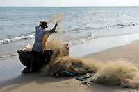 Fisherman unloading net from coracle fishing boat (Thung chai). Mui Ne, Vietnam