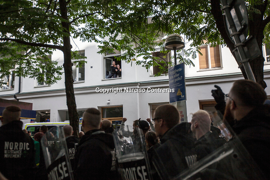 August 25, 2018: Anti-fascist supporters yell slogans from a window against their opponents and members of the neo Nazi Nordic Resistance Movement NRM (Nordiska motståndsrörelsen) during a demonstration at the Kungsholmstorg square in Stockholm, Sweden. An estimate of 200 supporters of the neo-Nazi organisation held a six-hour rally guarded by a strong police deployment.