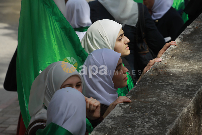 Palestinian women hold Hamas movement's flags during the funeral of Palestinian militant Mohammed Hanbali who was killed 11 years ago during a funeral in the West Bank city of Nablus, March 19, 2014. Since the late 1960s, Israel has withheld the bodies of hundreds of Palestinians. Their bodies are interred in numbered, rather than named, graves in four cemeteries created for that purpose, the biggest of which is located in the Jordan Valley. Photo by Nedal Eshtayah