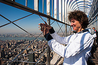 former women's national team player Michelle Akers takes a photo from the observation deck of the Empire State Building after US Soccer fliped the switch to light the Empire State Building in the Red White and Blue colors of the US Soccer Federation during the centennial celebration of U. S. Soccer in New York, NY, on April 05, 2013.