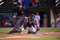 Columbus Clippers catcher Adam Moore (25) swipes the tag at Eddie Rosario (not pictured) scoring the game winning run as umpire Joe Born looks on to make the call during a game against the Rochester Red Wings on June 14, 2016 at Frontier Field in Rochester, New York.  Rochester defeated Columbus 1-0.  (Mike Janes/Four Seam Images)