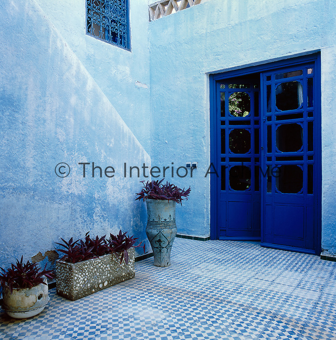 The courtyard entrance is decorated in cool blues with rustic stone pots on the tiled floor.