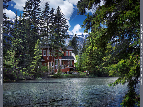 Beautiful spring nature scenery of a large waterfront family house in Canmore, town in Alberta Rockies, Bow valley, with tall trees and Rocky mountains in the background. Canmore, Alberta, Canada.