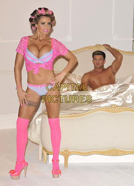 Katie Price (Jordan) & Leandro Penna.The launch photocall for Katie Price's new summer lingerie range for Store 21, The Worx, London, England..May 29th, 2012.full length pink lace top knotted bra cleavage belly stomach midriff knickers underwear tights stockings tattoo garter beige platform sandals shoes rollers curlers in hair side bed chest topless couple hand on hip pointing funny .CAP/CAN.©Can Nguyen/Capital Pictures.