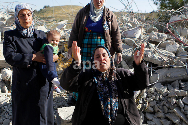 Palestinians collect belongings near the rubble of their house that were demolished by the Israeli army, after Israeli authorities said it was built without a permit, in the village of Sourif the west bank city of Hebron, on April 4, 2016. Photo by Wisam Hashlamoun