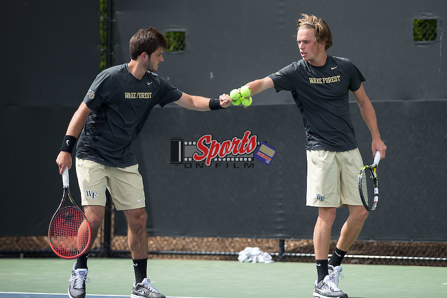 Keivon Tabrizi (left) and Romain Bogaerts of the Wake Forest Demon Deacons bump fists during their doubles match against the North Carolina Tar Heels at the Wake Forest Tennis Center on April 11, 2015 in Winston-Salem, North Carolina.  The Demon Deacons defeated the Tar Heels 4-3.    (Brian Westerholt/Sports On Film)