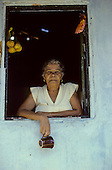 Recife, Brazil. Woman with dangling cup in the window of her shack shop in a poor area.