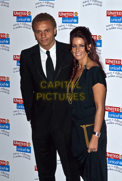 "WES BROWN (Wesley Michael ""Wes"" Brown) & LEANNE WASSELL.Attending the United for UNICEF Gala Dinner at Old Trafford in Manchester, England, UK, November 29th 2009..full length black suit tie white shirt footballer WAG black dress married couple husband wife gold necklace hand in pocket .CAP/AT.©Alan Towse/Capital Pictures"