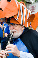 Clarinetist with fish puppet representing creatures who live in water. MayDay Parade and Festival. Minneapolis Minnesota USA