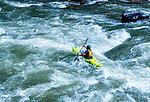 A man rides a kayak on the Gallatin River in Montana. People kayak on the Gallatin Rvier, between Big Sky and Bozeman, Montana.
