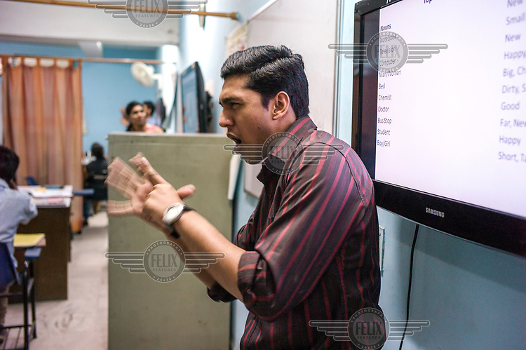 A tutor signs lessons for deaf students in a classroom at the Noida Deaf Society.
