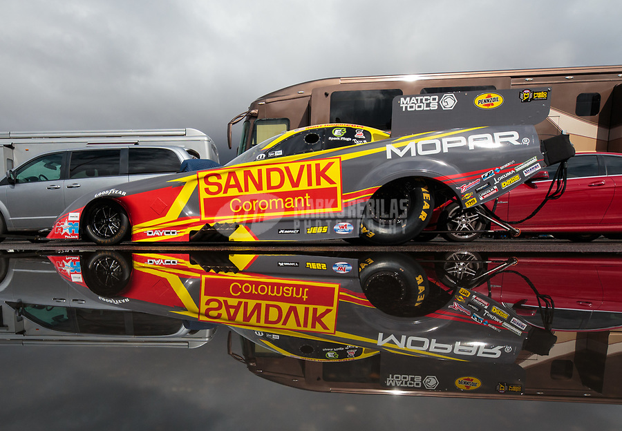 Feb 22, 2019; Chandler, AZ, USA; The car of NHRA funny car driver Matt Hagan reflects in a rain puddle as the car is towed to the staging lanes during qualifying for the Arizona Nationals at Wild Horse Pass Motorsports Park. Mandatory Credit: Mark J. Rebilas-USA TODAY Sports