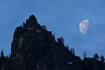 Waning gibbous moon setting over rock spire, Yosemite National Park, California