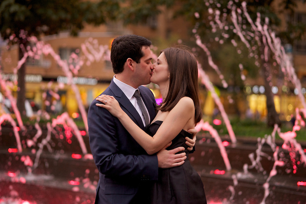The couple kissing with the fountain and glowing lights in the background.