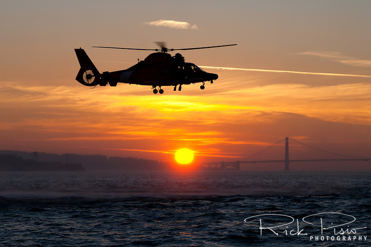 A Coast Guard HH-65 Dolphin helicopter hovers above the waters of San Francisco Bay. The helicopter and crew, based at U.S. Coast Guard Air Station San Francisco, was on a practice mission to maintain qualifications and search and rescue proficiency.