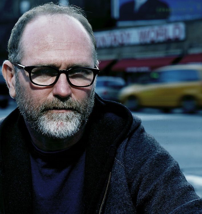 Close up of a middle aged man with a grey beard wearing dark rimmed glasses
