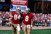 SAN FRANCISCO, CA - Quarterback Steve Young of the San Francisco 49ers walks off the field with teammate Brent Jones during a game at Candlestick Park in San Francisco, California in 1997. Photo by Brad Mangin