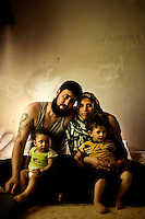 27 year old Jalal Ahmed Aziza with his son, daughter and pregnant wife in a 10m2 room they live in at the Cyber City Refugee Camp. This former electronics factory has been turned into a refugee camp for displaced Syrians, mostly of Palestinian origin. The six floor building is home to about 500 refugees. They are from Dera in Syria but have been living here for 2 years. He says that he was imprisoned for 60 days, for supporting the revolution, until his father managed to get him out by paying 5000 USD, after that he fled to Jordan and ended up here. He says he hates the place and despite the obvious danger he talks about going back to Syria to fight with the FSA. Approximately two million people have fled the conflict in Syria since it began in 2011, with nearly half a million in Jordan.