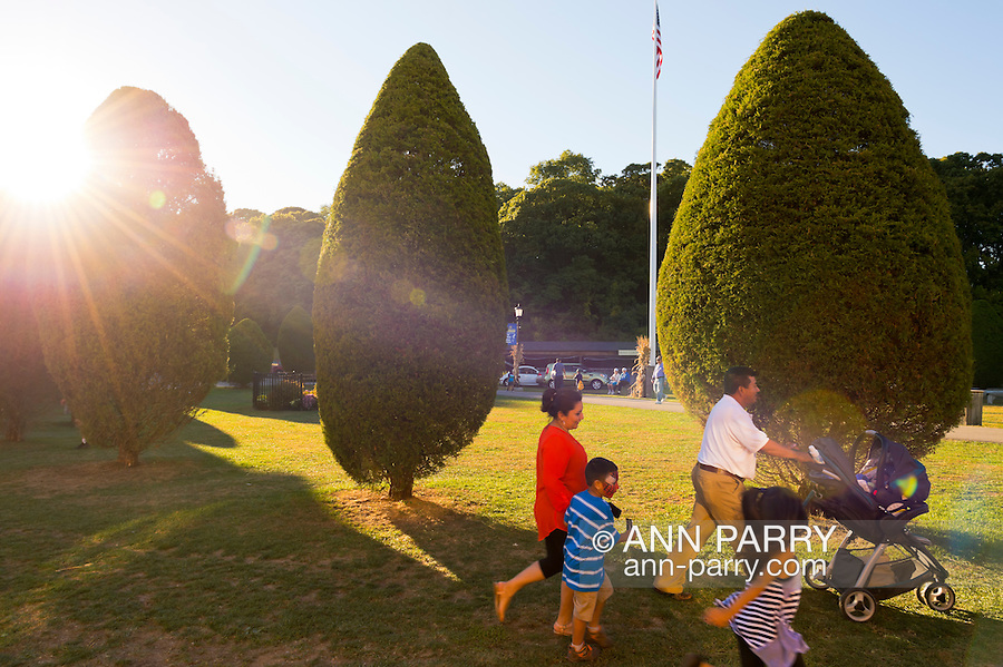 Old Bethpage, New York, U.S. 29th September 2013. Leaving The Long Island Fair, a family passes by conical evergreen trees when closing time arrives. A yearly event since 1842, the county fair is now held at a reconstructed fairground at Old Bethpage Village Restoration.