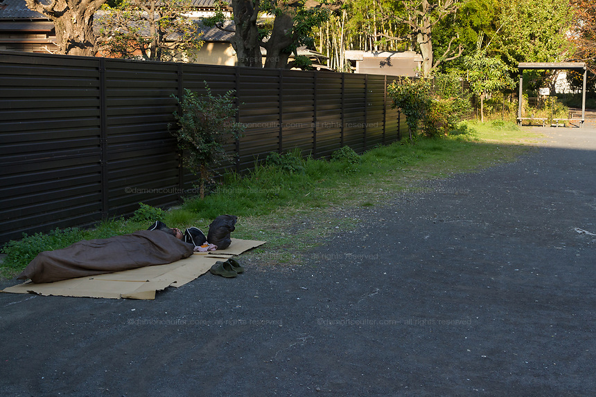 A homeless man sleeps rough in a park in Shinjuku, Tokyo, Japan Wednesday November 21st