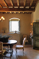 This dining room is furnished with a solid wood table surrounded by chairs upholstered in toile de Jouy