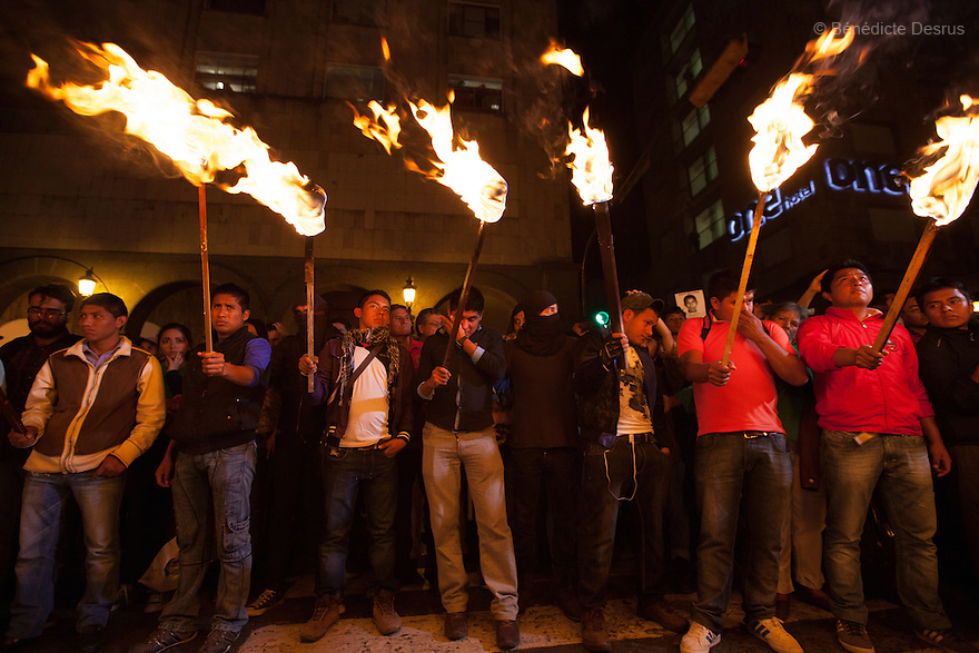 Parents and classmates of the 43 missing students from Ayotzinapa's teacher training college hold 43 torches and images of the missing students during a march in Guadalajara, Jalisco, Mexico on November 18, 2014. The relatives of the 43 missing students still do not believe the official line that the young men are all dead, and with classmates, social organizations and human rights defenders, they started on Thursday a national caravan. They split up into three different caravans, branching out to share information face to face with supporters in other cities and rally nationwide support. The three groups will meet in Mexico City on Thursday 20 for a general strike and massive marches to demand justice and fight against corrupted government and organized crime. Criticism of the government has intensified in Mexico, and many are demanding that the search for the 43 missing students continue until there is concrete evidence to the contrary. (Photo by Bénédicte Desrus)