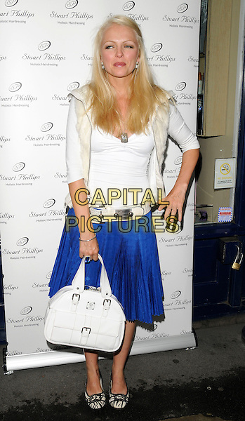 HANNAH  SANDLING .Stuart Phillips Salon 15th Anniversary Party at Covent Garden, London, England, UK, July 15th 2009.full length blue skirt white top bag satchel bowling shoes flats flat belt .CAP/CAN.©Can Nguyen/Capital Pictures