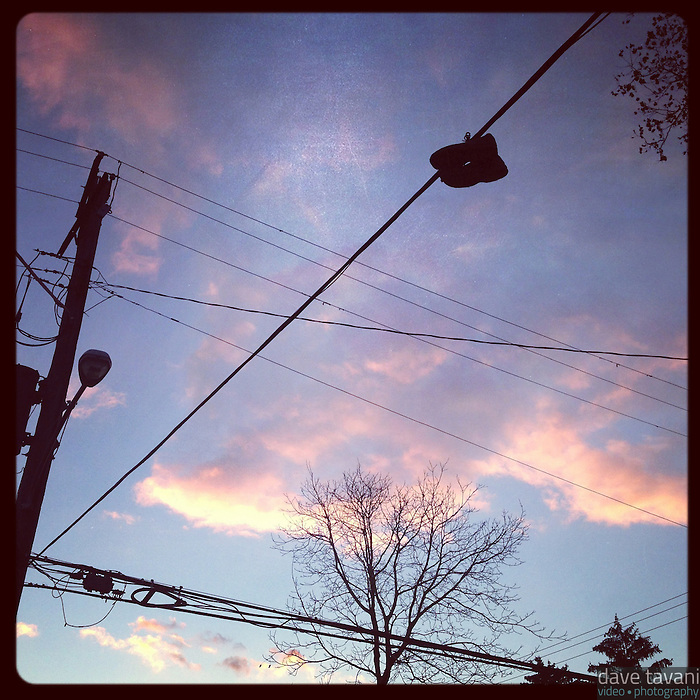 A pair of shoes dangle on a wire silhouetted by the last light of the day on Cherokee Street in the Germantown section of Philadelphia on November 24, 2012.