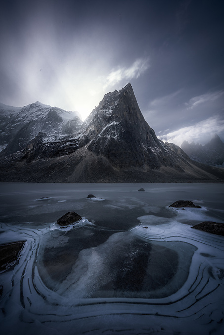 On the heels of winter in this far north, the sun never fully rises or sets.  Here, just before twilight, sunbeams radiate from behind the impressive granite peaks, framed by an interesting spiral formation on a frozen lake below.