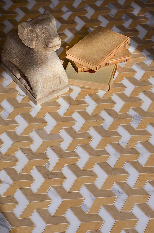 Francois Grand, a waterjet mosaic shown in polished Calacatta Tia, honed Sylvia Gold and honed Lagos Gold, is part of the Illusions® collection by New Ravenna.