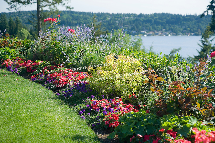 a curving lawn of perfectly manicured green grass is edged by a curved border of mixed annuals, perennials and shrubs before the property drops off a steep grade and falls away to the lake just beyond
