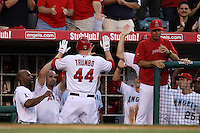 Mark Trumbo  #44 of the Los Angeles Angels is greeted by teammates after hitting a home run against the San Francisco Giants at Angel Stadium on June 18, 2012 in Anaheim, California. San Francisco defeated Los Angeles 5-3. (Larry Goren/Four Seam Images)