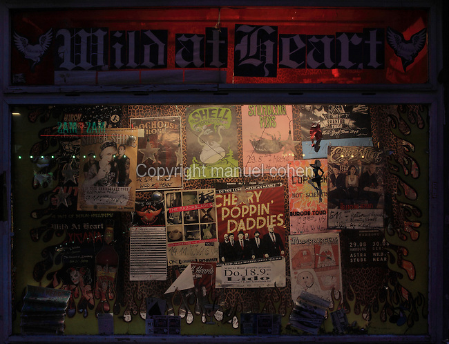 Promotional posters on the wall of a cafe at nighttime, Oranienstrasse, Berlin, Germany. Picture by Manuel Cohen