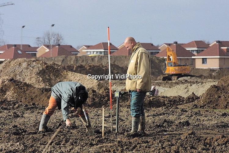 Foto: VidiPhoto..LENT - Munitiespecialisten van het explosieven-opruimingsbedrijf Saricon controleren het bouwterrein in de Nijmeegse Waalsprong op de aanwezigheid van oorlogsresten. Het voormalige kassengebied van Lent was in het laatste jaar van de Tweede Wereldoorlog frontlinie. Vermoedelijk tienduizenden stuks -soms levensgevaarlijke- restanten van bommen en granaten bevinden zich nog steeds in de grond. Het is voor de eerste keer dat in Nederland een complete Vinex-locatie (1300 hectare) centimeter voor centimeter wordt afgezocht met detectie-apparatuur.