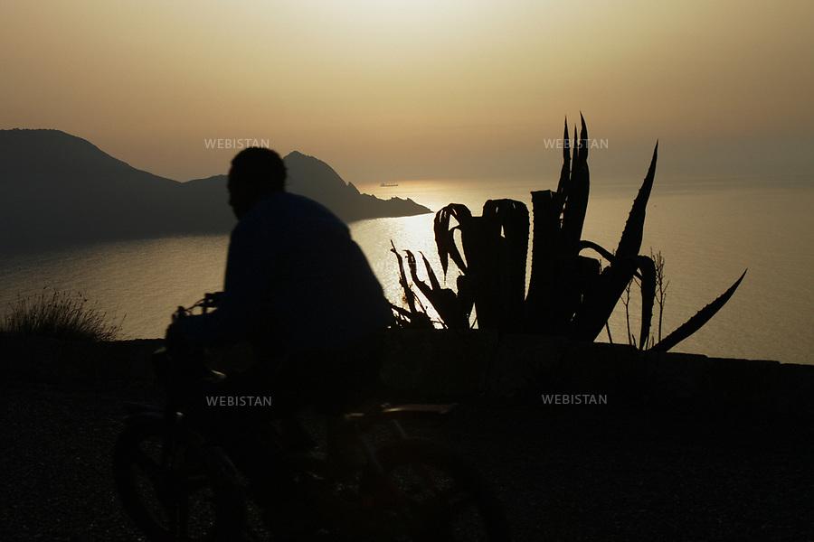 Algerie. Oran. 08 Avril 2011.Un homme roule a moto avec une vue sur une cote oranaise, au crepuscule et un agave.<br /> <br /> <br /> Algeria, Oran. April 8th 2011<br /> A man drives a motorcycle with a side view of Oran, at dusk and an agave plant.