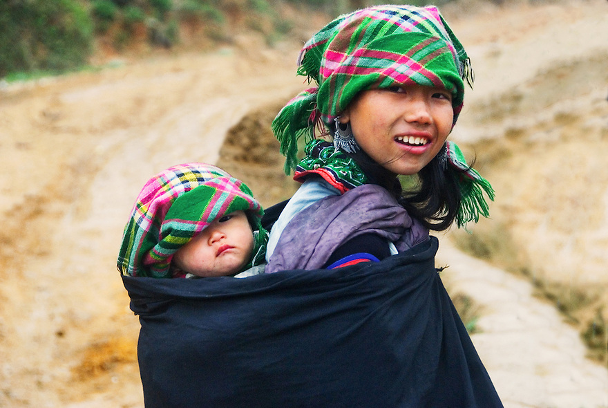 A mother and daughter walk along terraced slopes outide Sapa, Vietnam.