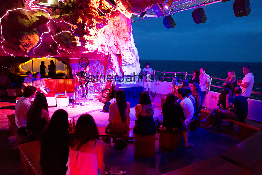 Spain, Menorca, Cala en Porter: Live music performance inside Cova d'en Xoroi bar built in cliff caves in evening | Spanien, Menorca, Cala en Porter: Live Music am Abaend in der Bar Cova d'en Xoroi in einer Felshoehle
