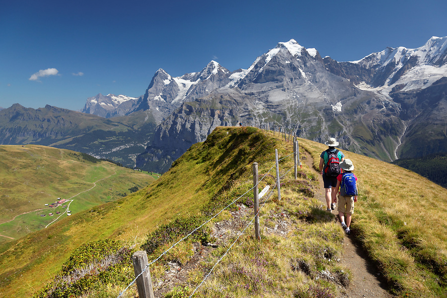 Woman and girl hiking on Wasenegg ridge on Schilthorn mountain, Eiger, Mönch and Jungfrau in background, Switzerland