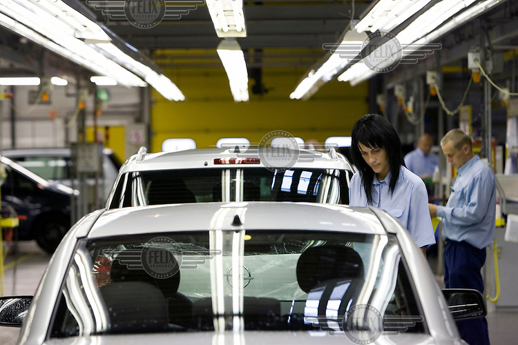A female factory worker checks the quality of the production at the end of an assembly line at the General Motors (GM) car manufacturing plant.