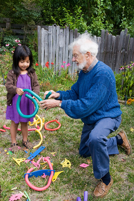 Berkeley CA Grandpa supervising adopted,four-year-old, Guatemalan granddaughter's construction play with flexible tubes MR