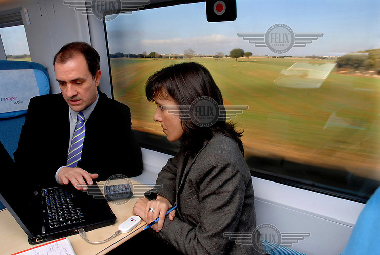 Two employees of Damm Brewers use a laptop together as they travel between Madrid and Barcelona on the AVE (Alta Velocidad Espanola) high-speed train.