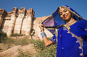 Rajasthani girl in traditional clothes with Mehrangarh Fort in background, Jodphur, Rajasthan, India --- Model Released