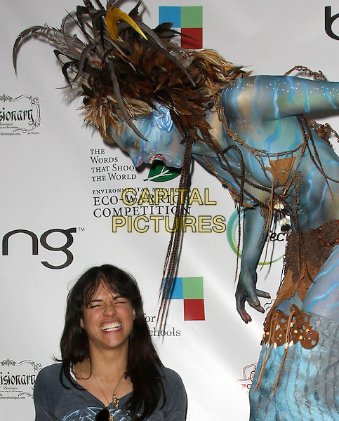 MICHELLE RODRIGUEZ & Avatar' Neytiri.40th Annivesary of Earth Day held At The JW Marriott LA Live, Los Angeles, California, USA, 22nd April 2010..half length fringe grey gray top necklace blue face body paint brown feather feathers headdress costume make-up funny smiling eyes shut laughing  tall short stilts .CAP/ADM/KB.©Kevan Brooks/AdMedia/Capital Pictures.