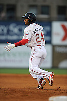 Second baseman Yoan Moncada (24) of the Greenville Drive takes a lead off first in a game against the Lexington Legends on Monday, May 18, 2015, at Fluor Field at the West End in Greenville, South Carolina. Moncada, a 19-year-old prospect from Cuba, made his professional debut tonight in the Red Sox organization. (Tom Priddy/Four Seam Images)