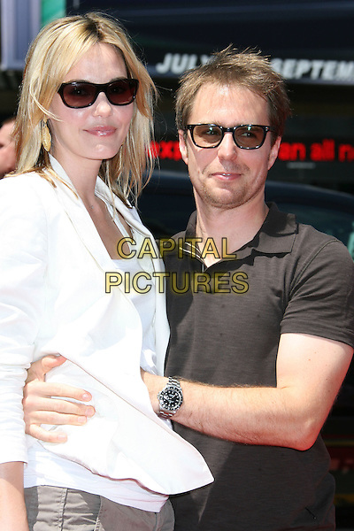 """LESLIE BIBB & SAM ROCKWELL.""""G-Force"""" World Premiere held at the El Capitan Theatre, Hollywood, California, USA..July 19th, 2009.half length white top jacket black side view couple arms around waist sunglasses shades .CAP/ADM/MJ.©Michael Jade/AdMedia/Capital Pictures."""