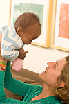 9 month old baby boy happy interaction with mother held high, adopted from Ethiopia