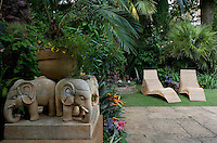 View towards a pair of sun-loungers in the garden past a plinth with carved stone elephants