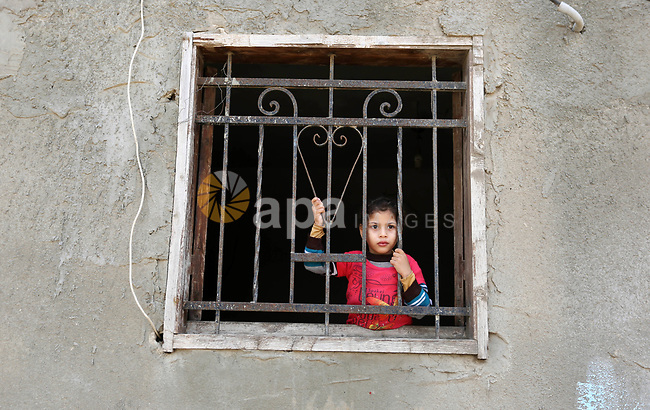 A Palestinian girl looks through a window during the funeral of Jabr Abu Mustafa, 42, who was shot dead by Israeli security forces during clashes at the Israel-Gaza border, during his funeral in Khan Younis in the southern Gaza Strip on May 12, 2018. Photo by Ashraf Amra